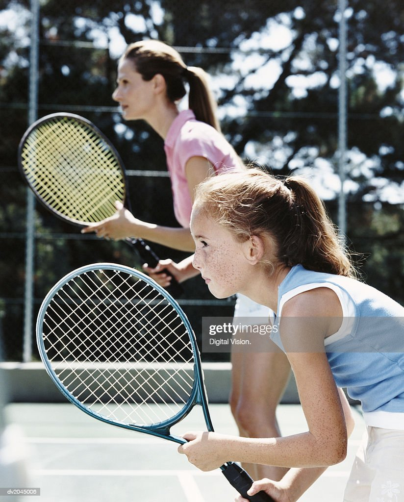 Profile of a Young Girl and Her Mother Standing on a Tennis Court Holding Their Raquets With Anticipation : Stock Photo