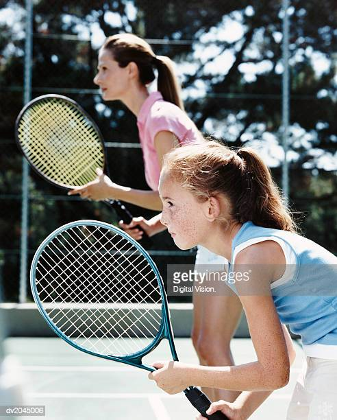 Profile of a Young Girl and Her Mother Standing on a Tennis Court Holding Their Raquets With Anticipation