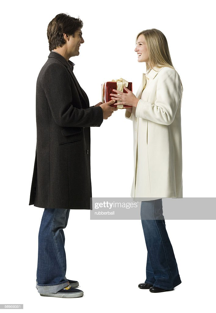Profile of a young man giving a gift to a young woman : ストックフォト