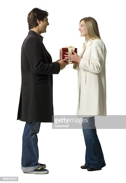 Profile of a young man giving a gift to a young woman
