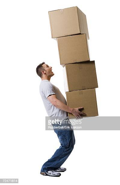 Profile of a young man holding a stack of cardboard boxes