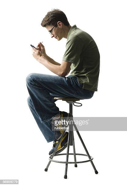 Profile of a young man sitting on a stool using a personal data assistant