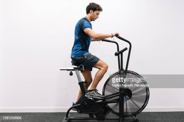 profile of a young man working out on an static bike at a gym - peloton stock pictures, royalty-free photos & images