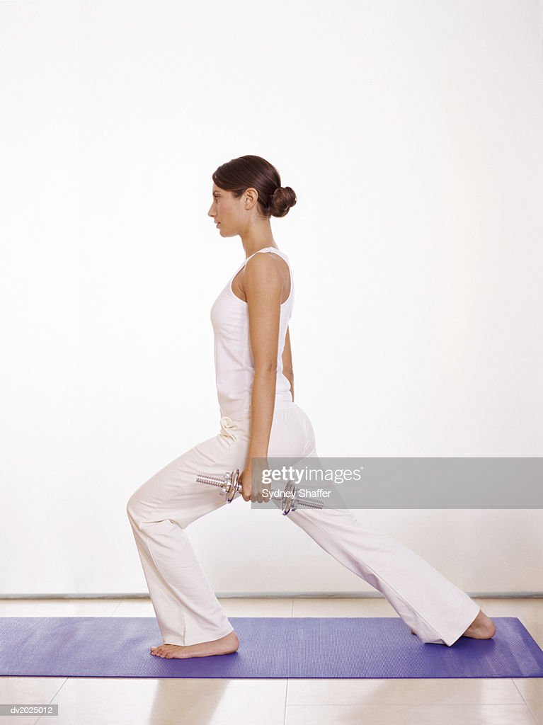 Profile of a Young Woman Doing Lunges on an Exercise Mat, Holding Dumbbells : Stock Photo