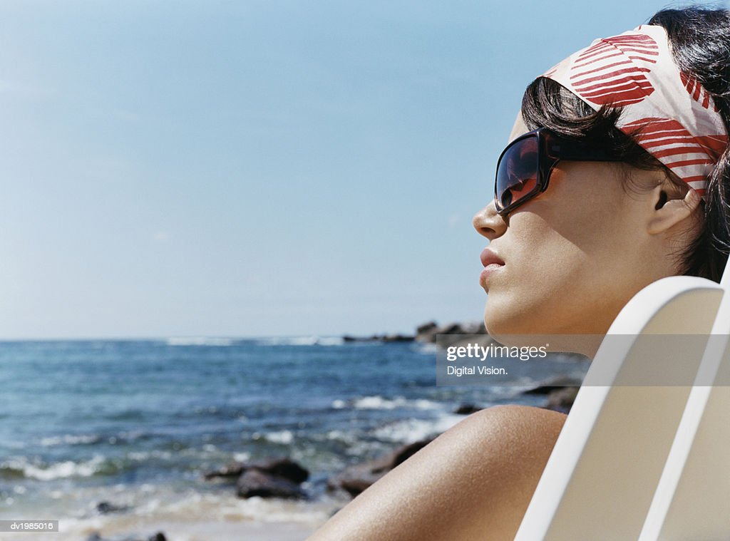 Profile of a Young Woman in Sunglasses Looking at the Sea : Stock Photo