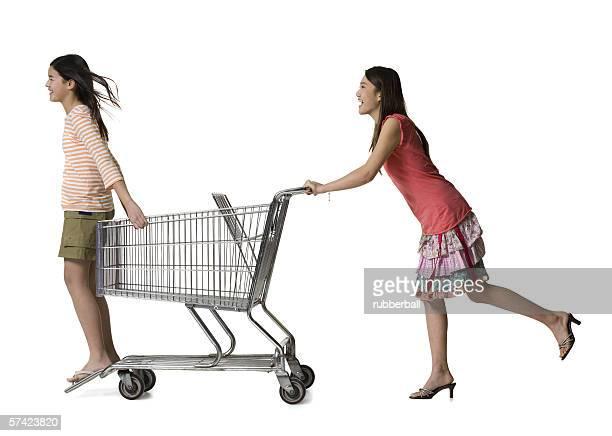 profile of a young woman pushing a teenage girl in a shopping cart - girls with short skirts - fotografias e filmes do acervo