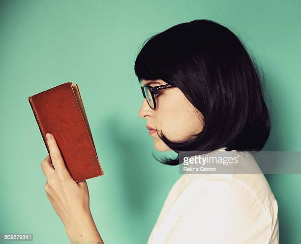 profile of a young woman reading a book - rekha garton stock pictures, royalty-free photos & images
