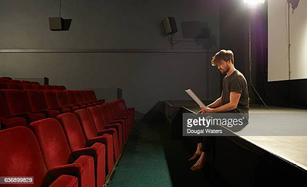 Profile of actor sitting on stage with script.