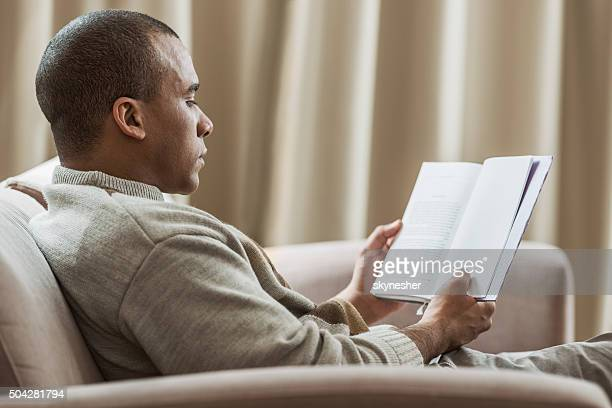 Profile of African America man reading book at home.