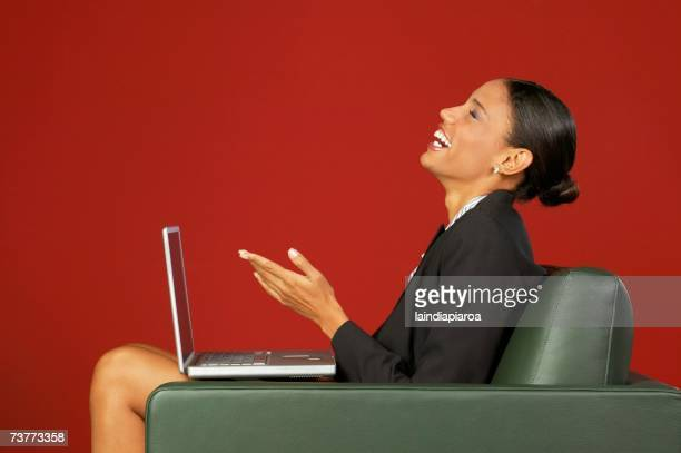 Profile of African businesswoman laughing with laptop in armchair