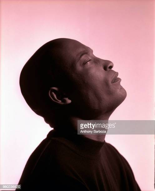 Profile of American film director John Singleton as he poses with his eyes closed and head tilted back against a rosecolored background Los Angeles...