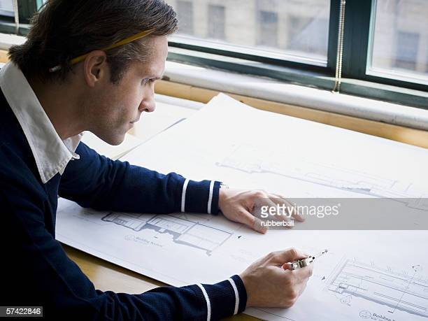 Profile of an architect working on a blueprint
