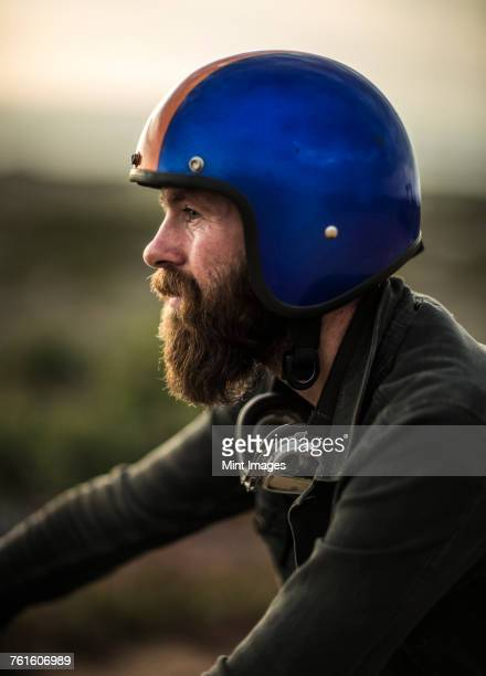 profile of bearded man wearing blue open face crash helmet, goggles round his neck. - バイクヘルメット ストックフォトと画像