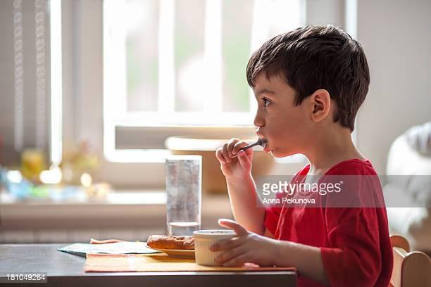 Profile of boy having breakfast