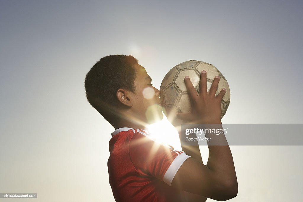 Profile of boy (12-13) kissing football, lens flare : Stock Photo