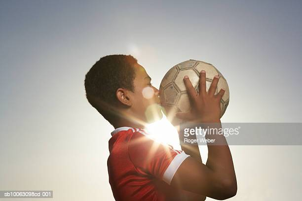Profile of boy (12-13) kissing football, lens flare
