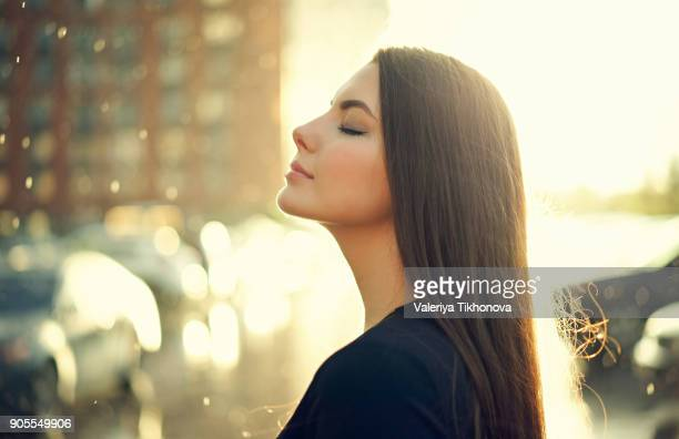 profile of caucasian woman outdoors with eyes closed - serene people stock photos and pictures