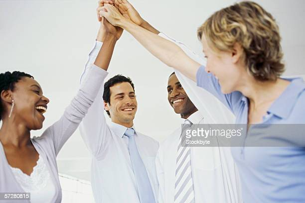 Profile of four businesspeople celebrating with high fives.