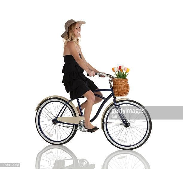 Perfil de feliz hermosa mujer montando una bicicleta