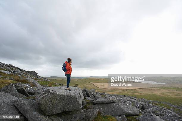 Profile of hiker looking out across rocky moorland