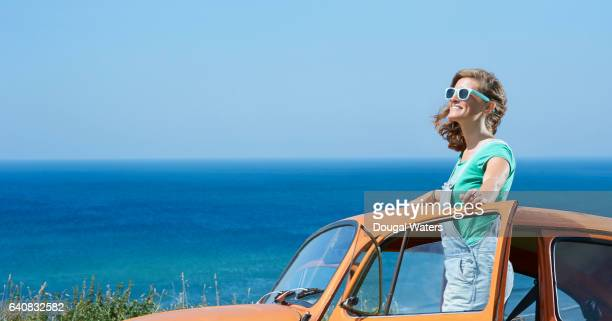 Profile of hipster woman on road trip with vintage car and blue sea.