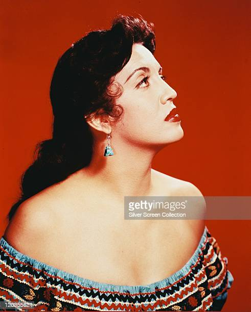 Profile of Katy Jurado Mexican actress wearing an offtheshoulder top in a studio portrait against a red background circa 1960