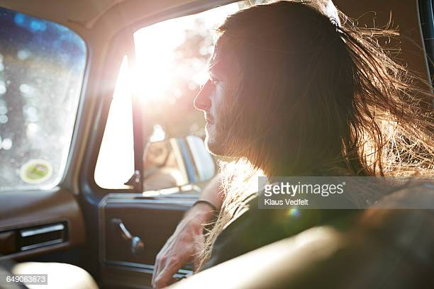 Profile of long haired guy inside car at sunset