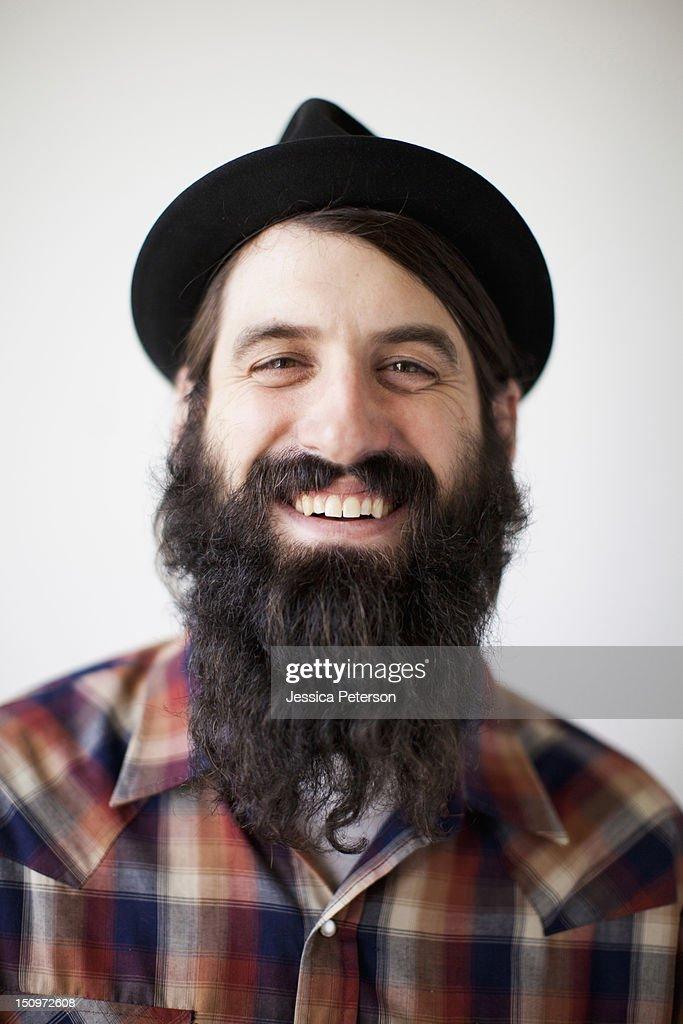 Profile of male character wearing long beard, hat and lumberjack shirt : Stock Photo