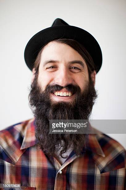 profile of male character wearing long beard, hat and lumberjack shirt - long hair stock pictures, royalty-free photos & images