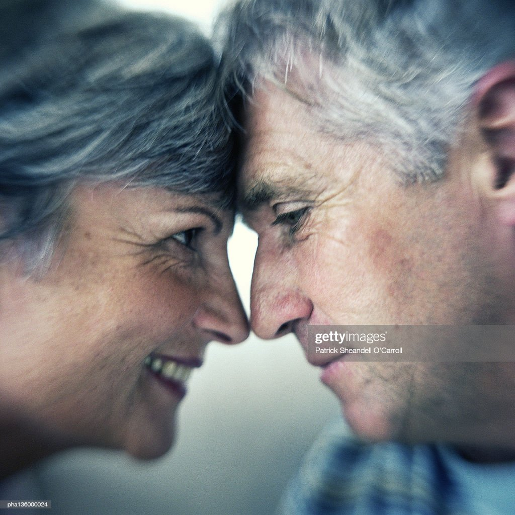 Profile of man and woman head to head and noses touching : Stockfoto