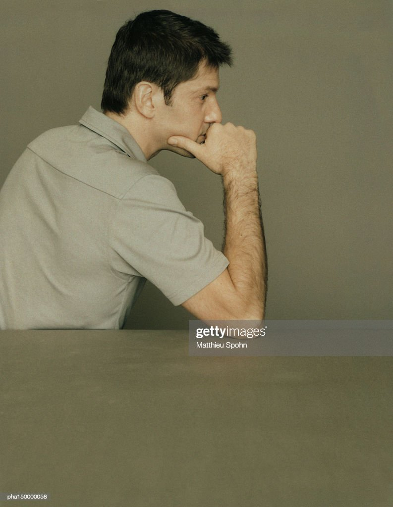 Profile of man leaning on elbow with hand under chin : Stockfoto