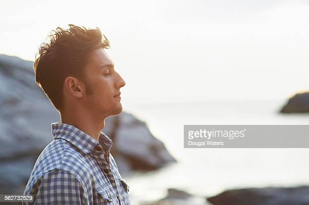 profile of man on rocky beach - tegenlicht stockfoto's en -beelden