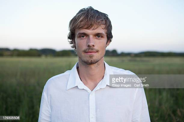 profile of man standing in field with white shirt on - 白いシャツ ストックフォトと画像