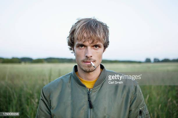 Profile of man standing in secluded field with cigarette hanging out of his mouth