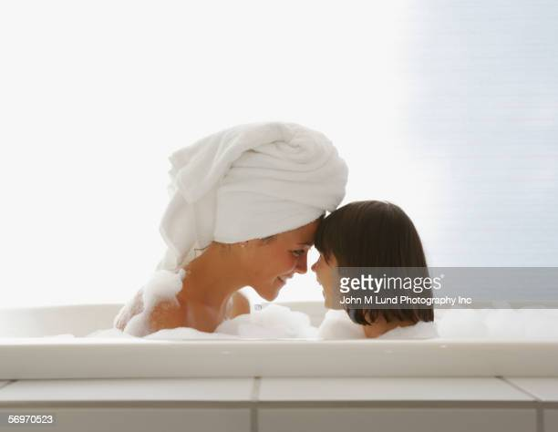 profile of mother and daughter touching foreheads in bubble bath - mother daughter towel stock photos and pictures