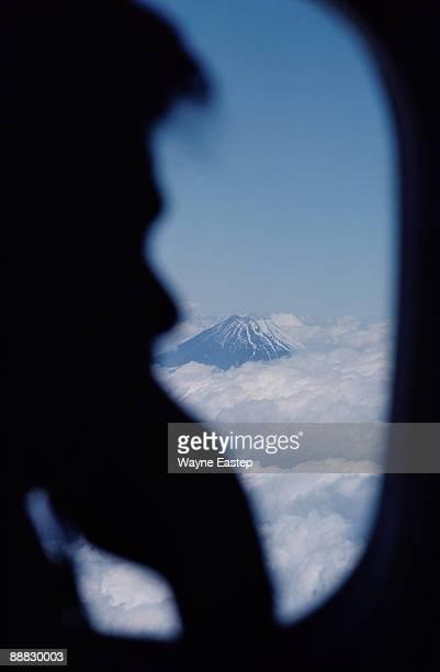 Profile of passenger on airplane near Mt. Fuji