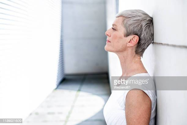 profile of pensive mature businesswoman leaning against wall - keratosis fotografías e imágenes de stock