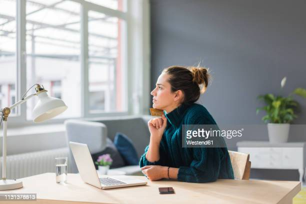 profile of pensive woman with laptop and credit card sitting at desk at home looking out of window - ongerust stockfoto's en -beelden