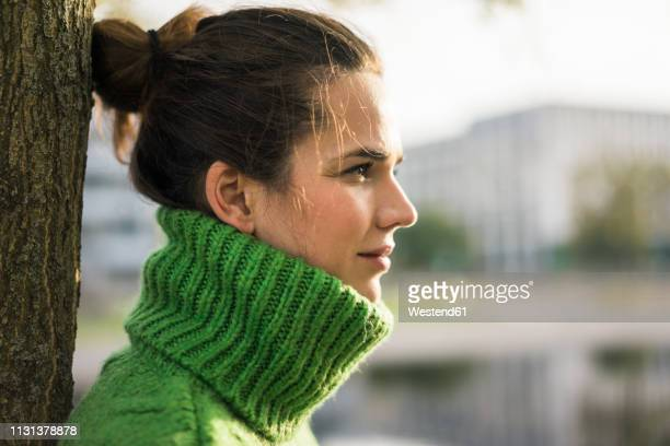 profile of relaxed woman wearing green turtleneck pullover leaning against tree trunk - col roulé photos et images de collection