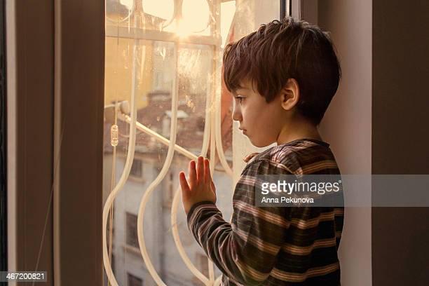 Profile of sad boy looking through the window