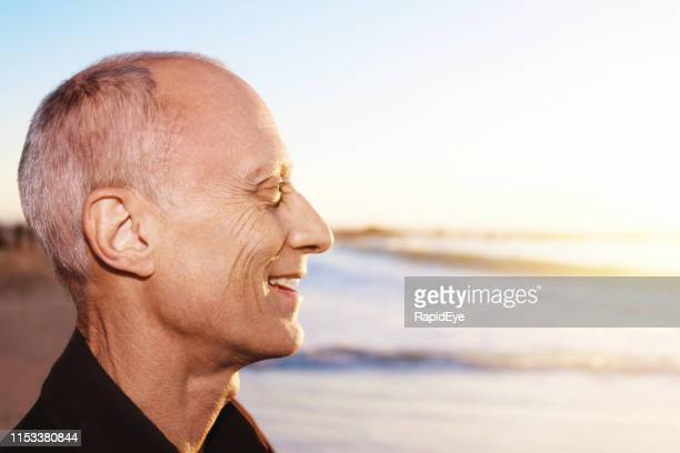 profile of senior man on beach, smiling happily in sunshine - cabeça humana imagens e fotografias de stock