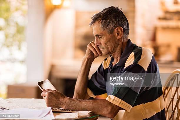 Profile of senior man reading something on digital tablet.