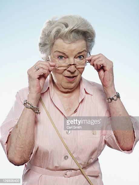 Profile of senior woman peering over her glasses