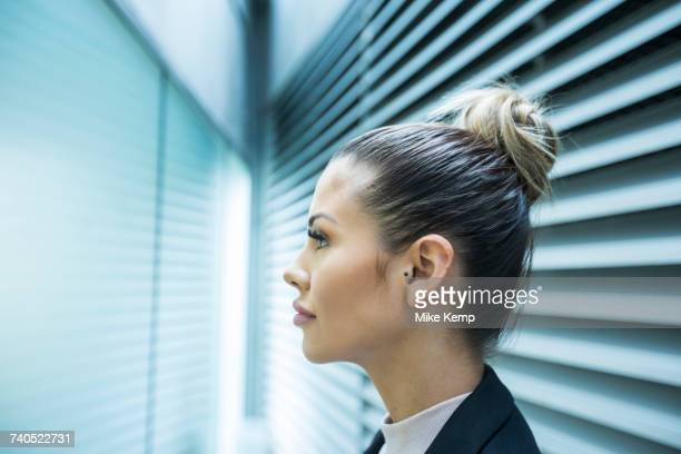 Profile of serious Mixed Race businesswoman in corridor