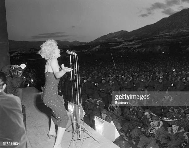 A profile of the celebrated Marilyn Monroe figure is given here in a picture made as she put on her act for a very enthusiastic GI audience in Korea...
