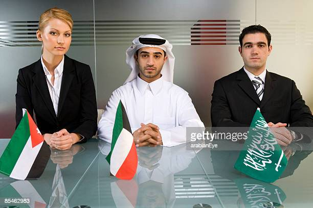 Profile of three business executives in a conference room and holding Arab flags.