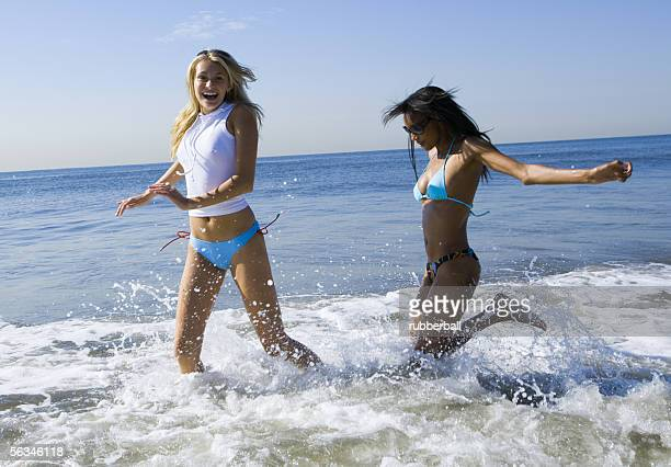 Profile of two young women wading in the sea water