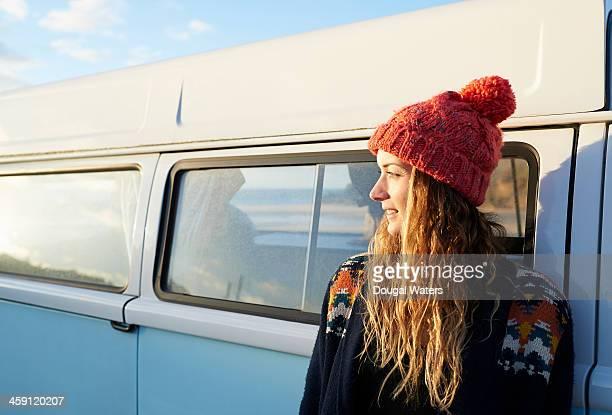 Profile of woman beside camper van.