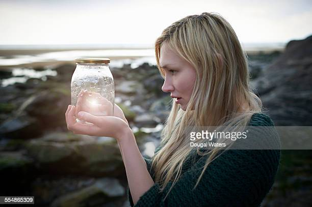 Profile of woman holding jam jar with glow.