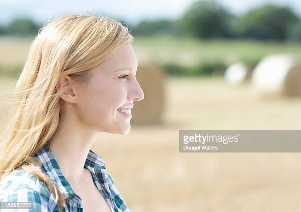 Profile of woman in countryside with bails of hay.